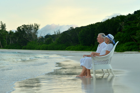 couple back to back: Elderly couple sitting on the shore and looks at sea