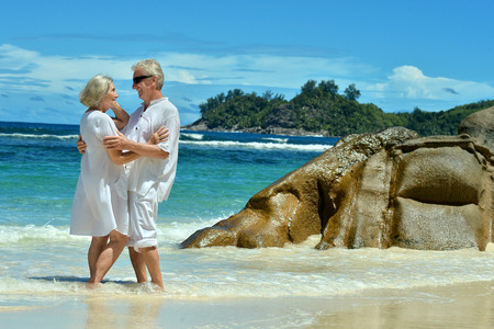 elderly: Beautiful elderly couple standing on the beach embracing