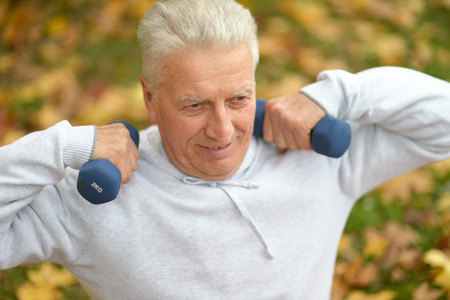 dumb bells: old man with dumb bells at nature Stock Photo