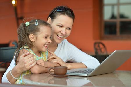 Mulher nova com a menina que usa o computador portátil Imagens