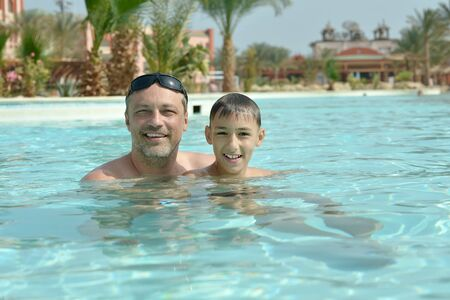 Happy smiling father with son in pool photo