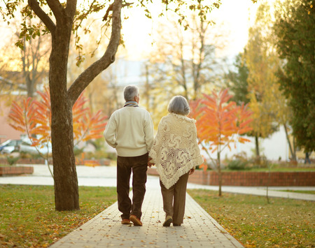 Happy elderly couple walking in autumn park