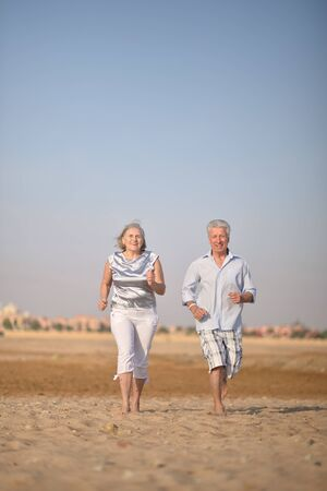 Portrait of a happy mature couple running on beach photo