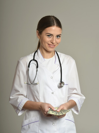 doctor money: Female doctor with money, standing on grey background Stock Photo