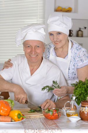 Portrait of an elderly couple preparing vegetable salad together photo