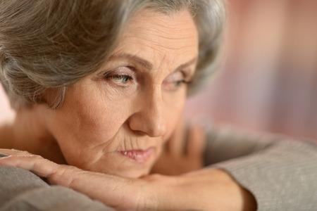 lamentable: Portrait of a sad mature woman on beige background