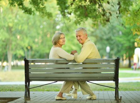 copule: Amusing senior couple sitting on bench in park
