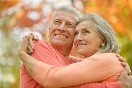 Portrait of happy senior couple hugging in autumn park photo
