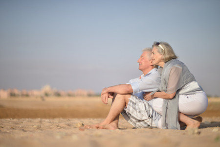 Amusing elderly couple went to the beach to enjoy the sea breeze 스톡 콘텐츠