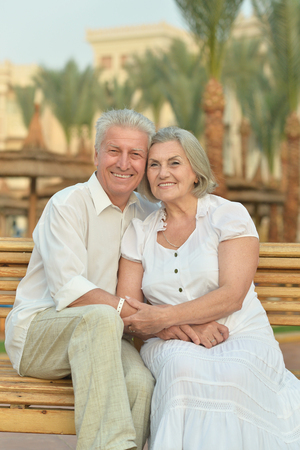 Senior couple sitting on bench at tropic hotel garden photo