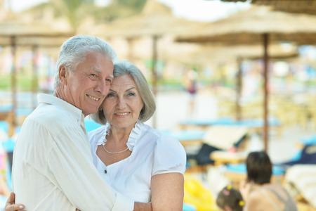 Amusing elderly couple having rest on beach Standard-Bild