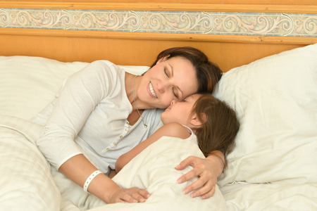 spending: Happy mother spending time with little daughter in bed