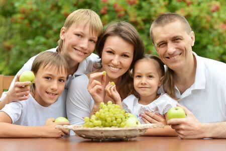 eating fruits: Familia de cinco frutas comer en mesa al aire libre en el horario de verano