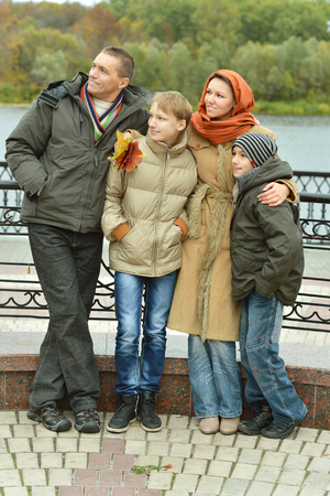 mam: Family of four sitting at river embankment in autumn