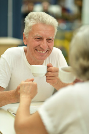 Portrait of an elderly couple on date drinking coffee photo