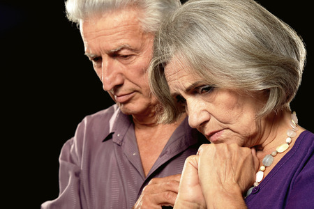 Sad elderly couple on a black background Standard-Bild