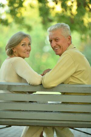 copule: Pareja de ancianos Divertido sentado en el banco en el parque