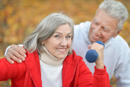 Happy fit senior couple exercising in autumn park photo