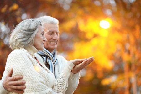 Idosos felizes bonitas no parque do outono Imagens