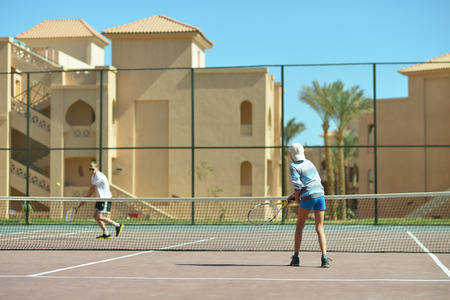 Two active brothers playing at tennis court photo