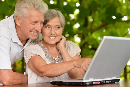 Happy senior couple sitting in summer at table with laptop Stock Photo