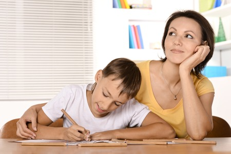 young mother: Mother and son are drawing together with pencils Stock Photo