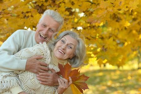 seniors: Portrait of happy senior couple hugging in autumn park Stock Photo