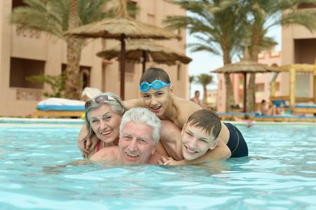Happy family having fun in a pool photo
