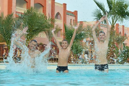 Happy father with sons in a pool photo