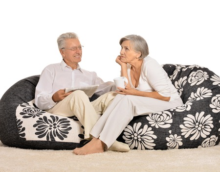 Happy elderly couple resting at home sitting on cushions photo