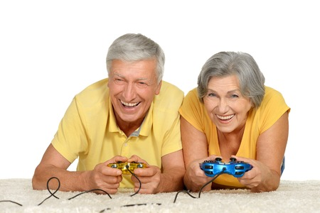 Mature couple plays video game at home on a white background