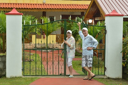 holiday home: Portrait of a beautiful elderly couple standing embracing outdoors