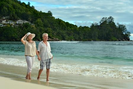 mujeres ancianas: Hermosa feliz pareja de ancianos caminando por la orilla del mar