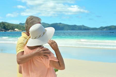 pareja abrazada: Hermosa feliz pareja de ancianos caminando por la orilla del mar