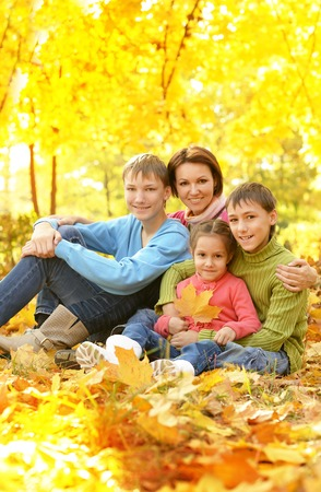Happy smiling family relaxing in autumn park Stock Photo