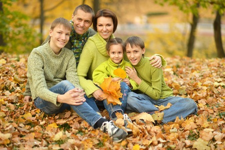 family portrait: Happy smiling family relaxing in autumn park Stock Photo