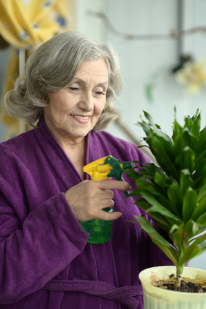 decorative balcony: Smiling positive aged woman watering decorative flowers on balcony Stock Photo