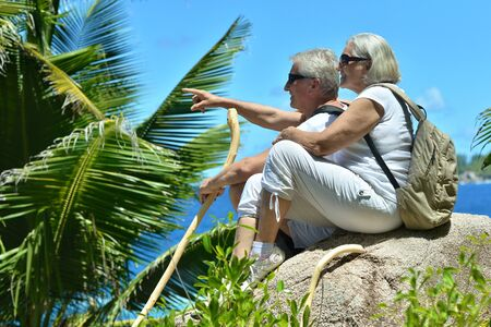 large rock: Happy beautiful elderly couple sitting on a large rock on the outside