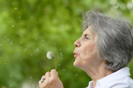 adulto mayor feliz: Retrato de una anciana en una caminata en el parque a finales de primavera Foto de archivo