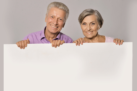 banner ad: Old age couple holding blank banner ad against white background Stock Photo