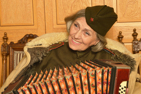 solder: Cute elderly woman solder playing accordion closeup Stock Photo