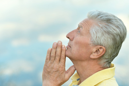 mid adult men: Thoughtful senior man prays in nature close-up