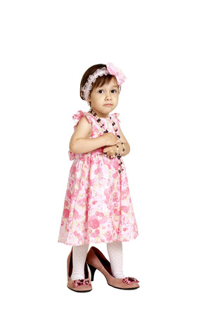 big shoes: Beautiful baby in a pink dress and big shoes stands on a white background