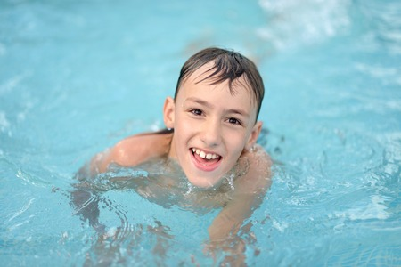 rubber ring: Happy teenage boy sweeming in pool with rubber ring Stock Photo