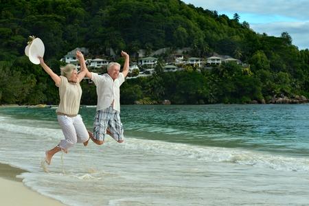 jubilados: Feliz pareja de ancianos saltando en la playa Foto de archivo