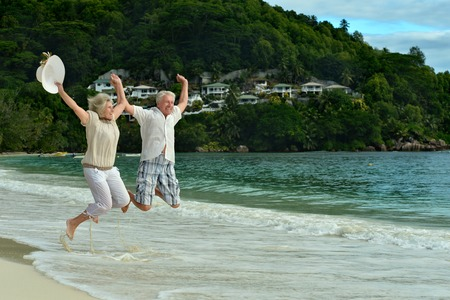 Happy elderly couple jumping on the beach Stockfoto