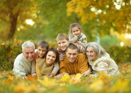 people sitting: Happy smiling family relaxing in autumn park Stock Photo