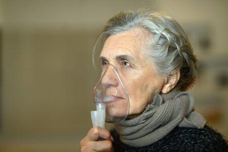 inhalation: Close-up of an elderly woman doing inhalation