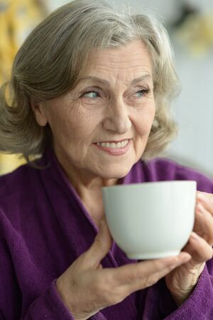 alone person: Portrait of senior woman with cup of coffee