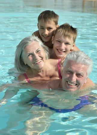 abuelos: Abuelos felices con sus nietos en la piscina en vacaciones